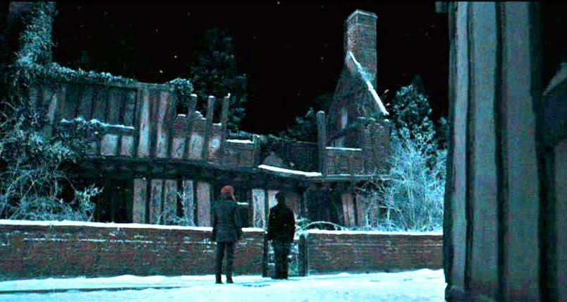 The ruin of Godrick's Hollow in Harry Potter and the Deathly Hallows: Part 1 with Harry and Hermione in the foreground looking at the house.