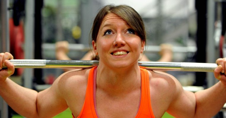 Female powerlifter in squat position under bar looking up.