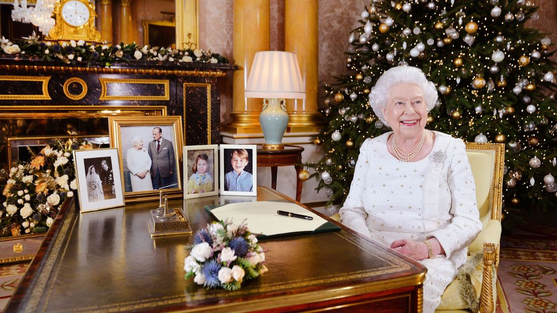 Queen Elizabeth of England sits smiling and laughing at a figure behind the cover sitting in beautiful, lavish surroundings