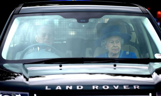 Front view into Land Rover driver by Prince Phillip with Queen Elizabeth in passenger seat.
