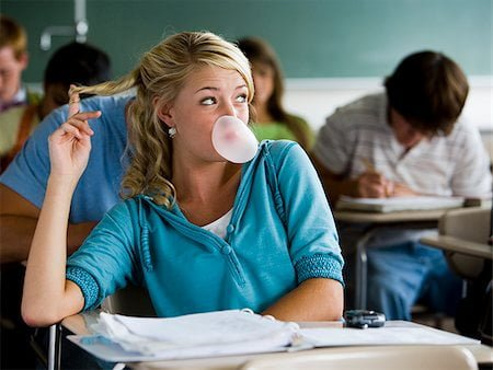 Female student sits in classroom blowing bubble with gum looking arrogantly out of the window