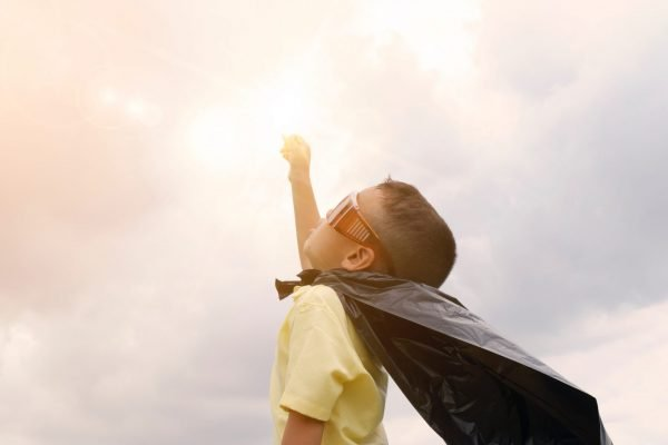 Young boy stands with a plastic bag as a cape with hand in the air towards the sun.