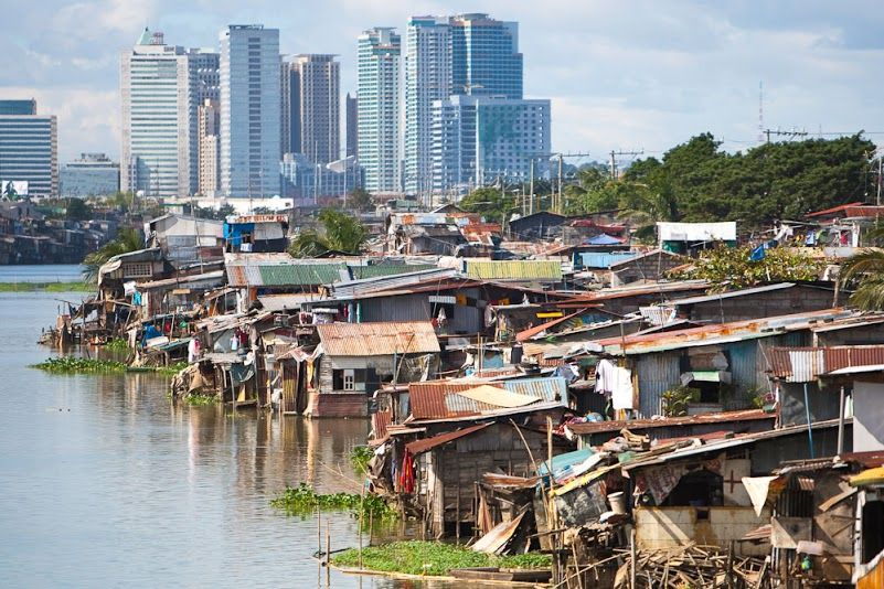 Impoverished slums in the foreground on riverbank contrasted with high-rise buildings in the background.