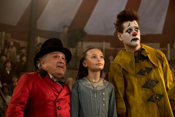 Characters from Dumbo from left to right: Danny Devito (Medici), Nico Parker (Milly), Collin Farrell (clown) look up towards top right of image