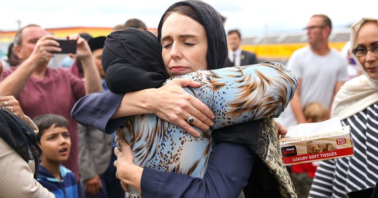 New Zealand Prime Minister Jacinda Ardern embraces muslim woman surrounded by crowd