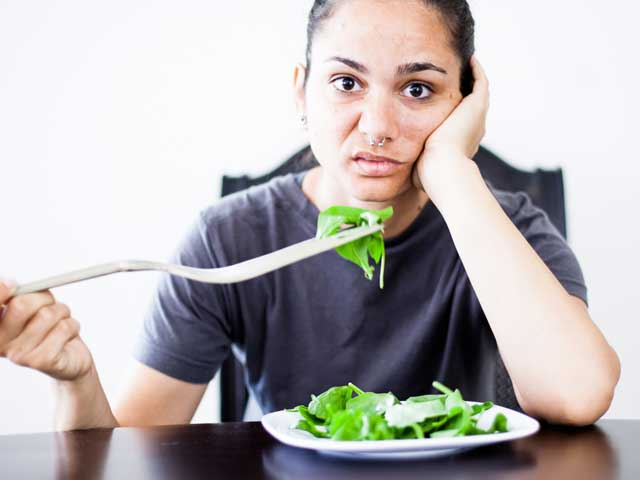 girl with septum piercing and grey t-shirt sits with plate of salad looking extremely disappointed