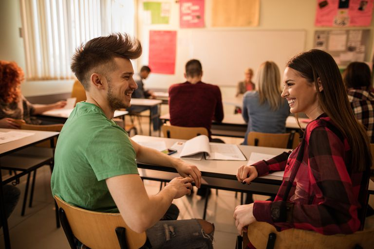 Man (left) and woman (right) face one another smiling in a language lesson. Other students and teacher in the background.