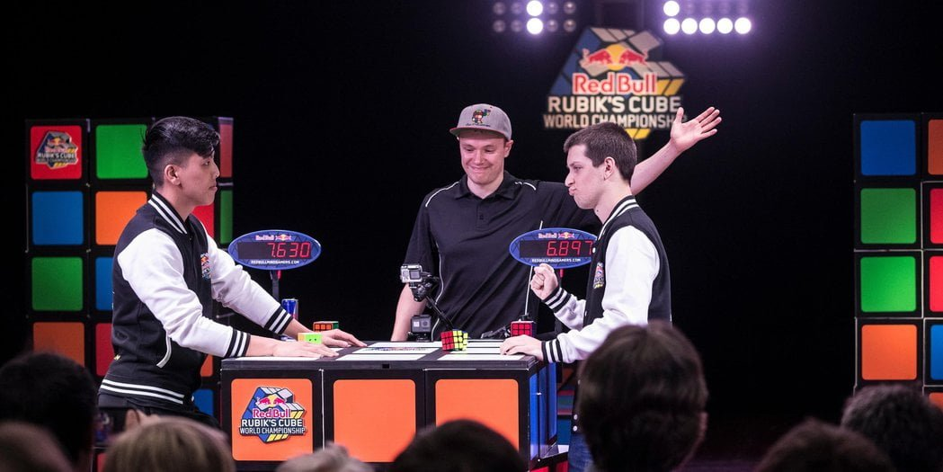 Two speed-cubing competitors stand with referee at centre who points to the person on the right that won the round