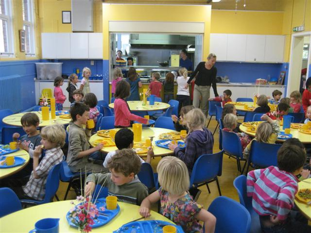 busy school canteen with teachers helping students at lunch