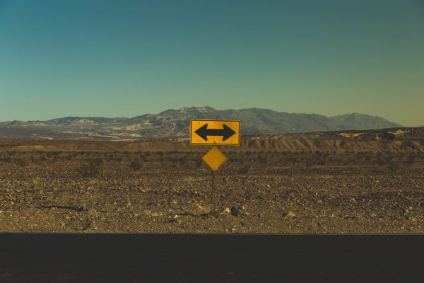 Sign next to deserted road with arrows pointing left and right